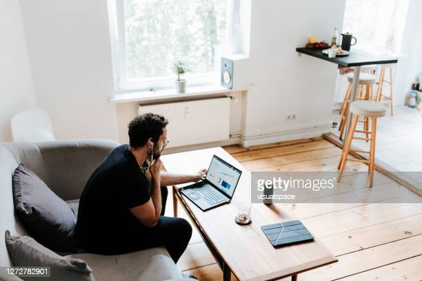 man works with laptop in his living room - wide shot stock pictures, royalty-free photos & images