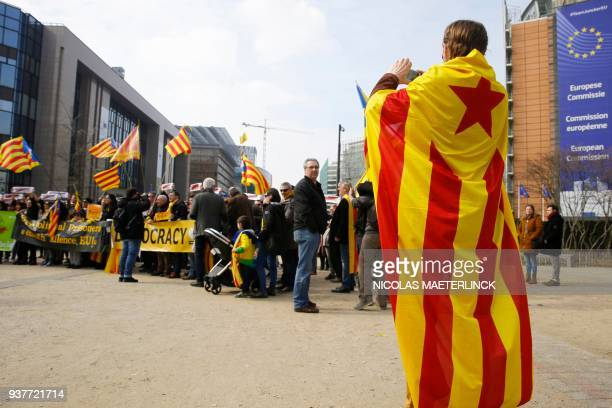 A man wrapped in a Catalan flag takes pictures of people taking part in a protest march of Catalans supporters in front of the European Commission's...