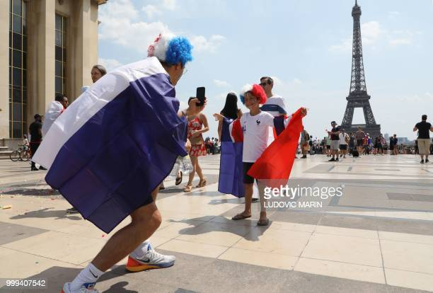 A man wrapped in a French national flag takes a pictures of a boy posing with a French flag in Front of the Eiffel Tower prior to the start of the...