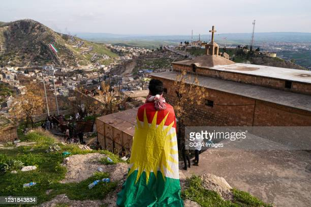Man wrapped in a Kurdistan flag standing next to a church during the Nowruz celebration. The town of Akre in the Duhok governorate celebrated Nowruz...