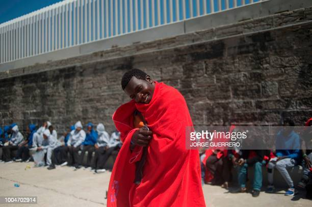 A man wrapped in a Red Cross blanket smiles after arriving aboard a coast guard boat at the harbour of Tarifa on July 24 after an inflatable boat...