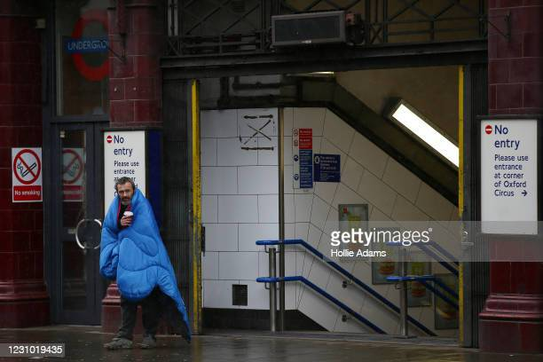 Man wrapped in a sleeping bag stands outside an Underground station as snow falls at Oxford Circus on February 7, 2021 in London, United Kingdom....