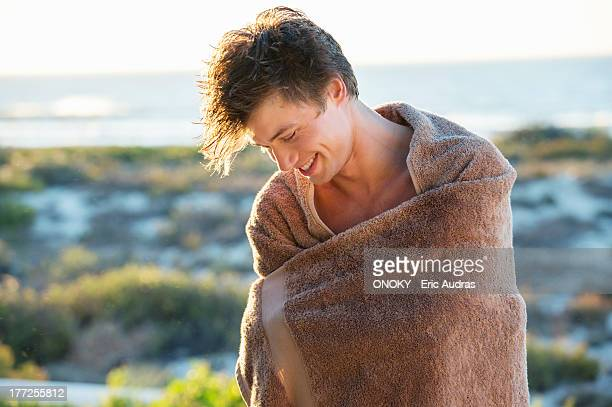 man wrapped in a towel standing on the beach - wrapped in a towel stock pictures, royalty-free photos & images