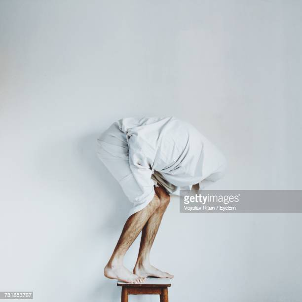 Man Wrapped In Blanket Bending While Standing On Stool Against White Wall
