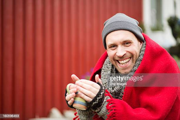 Man wrapped in blanket outdoors
