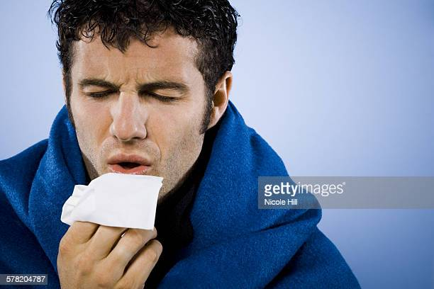 Man wrapped in blanket with tissue