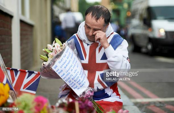 TOPSHOT A man wrapped in Britain's Union Flag prepares to lay flowers at a police cordon on Borough High Street near Borough Market in London on June...