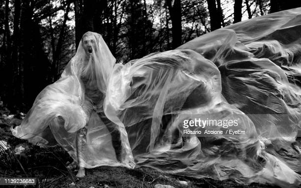 man wrapped in plastic while screaming at forest - man wrapped in plastic stock pictures, royalty-free photos & images