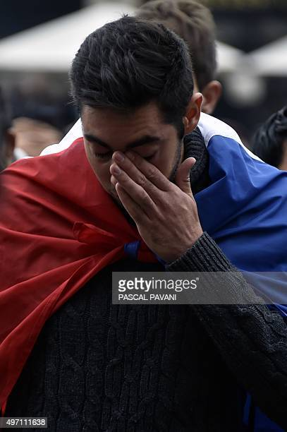 A man wrapped in the French flag reacts as people gather to pay tribute to the victims of a series of coordinated attacks in and around Paris in...