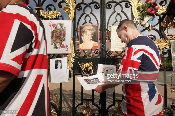 A man wrapped in Union Jack flags looks at tributes to Diana Princess of Wales placed on the gates of Kensington Palace on August 31 2009 in London...