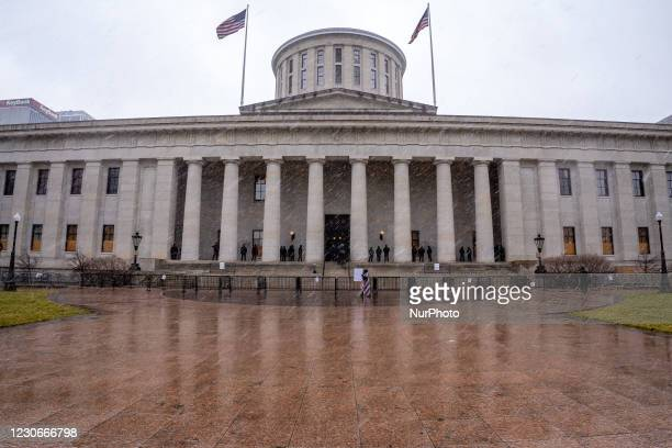Man wrapped in U.S. Flags paces back and forth past Ohio State Patrol officers standing guard during an armed protest at the Ohio Statehouse ahead of...
