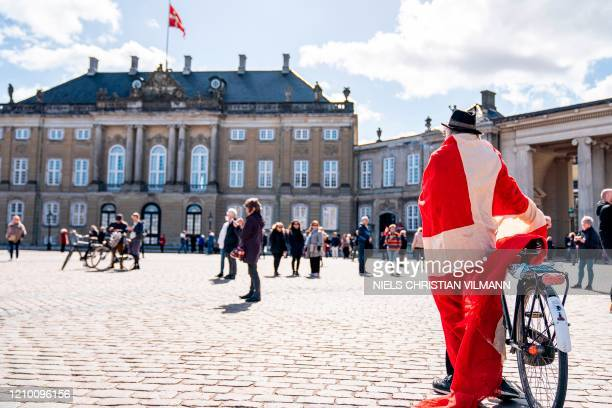 Man wrapped into a Danish flag stands at Amalienborg Palace Square, where people sang to mark the 80th birthday of Danish Queen Margrethe II, in...