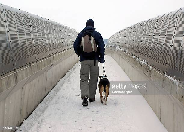 Man wrapped up warm walking dog across pedestrian bridge in the snow during cold winter.