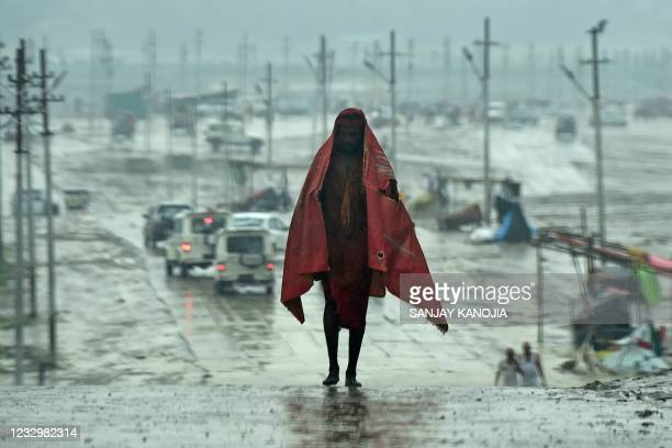 Man wraps a plastic sheet to cover himself as it rains in Allahabad on May 19, 2021.