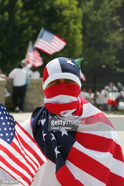 A man wraps his face and body in American flags during a rally on what is dubbed a Day Without Immigrants or the Great American Boycott day on May 1...