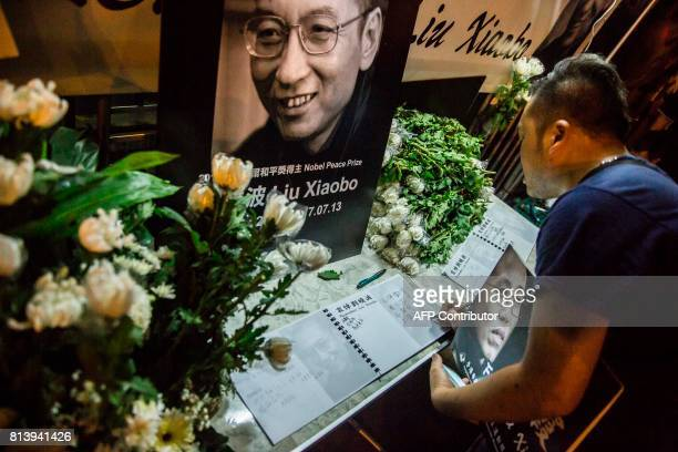 A man writes a message and holds a portrait outside the Chinese Liaison Office of Hong Kong after the death of Chinese Noble laureate Liu Xiaobo in...