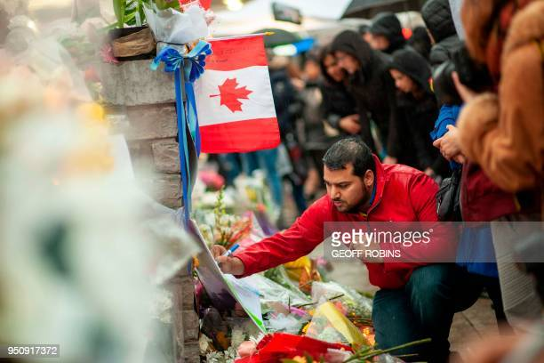 A man writes a message at a memorial near the site of the deadly van attack April 24 2018 in Toronto Ontario A van driver who ran over 10 people when...