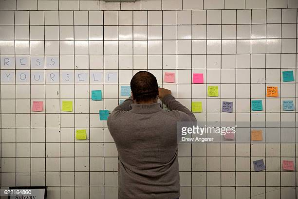 A man writes a message on a postit note as part of a public art project entitled 'Subway Therapy' at the 6th Avenue subway station November 10 2016...