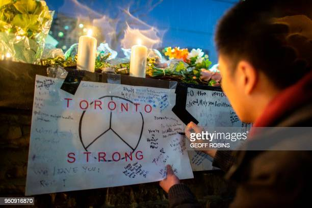 A man writes a message on a sign during a vigil April 24 2018 in Toronto Canada near the site of the previous day's deadly street van attack A van...