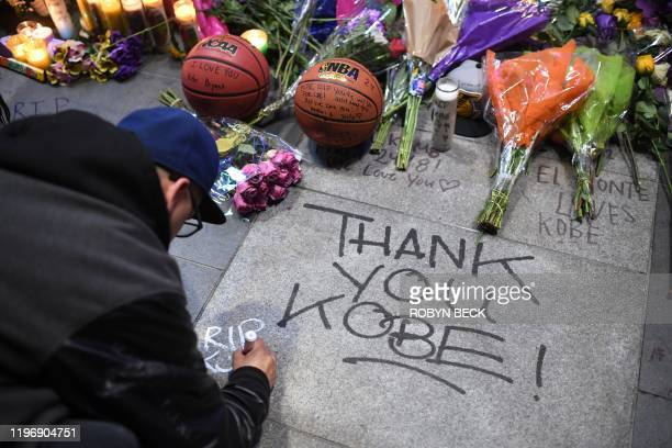 A man writes a message on the pavement near a makeshift memorial as fans gather to mourn the death of NBA legend Kobe Bryant who was killed along...