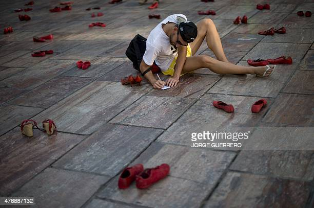 A man writes a note to put it in a pair of red shoes at the Constitucion square in Malaga where the Mexican artist Elina Chauvet's artinstallation...