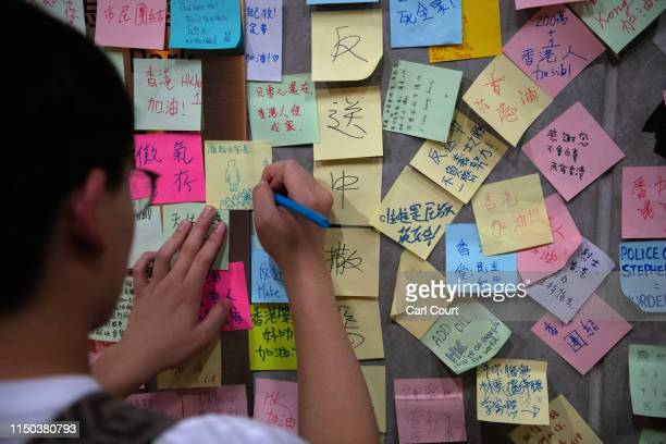 A man writes a protest message on postit note on the wall of a stairway near the Legislative Council building on June 17 2019 in Hong Kong Hong Kong...