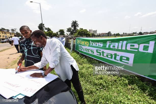 A man writes down slogans on a placard on the sidelines of a demonstration held to protest against the suspension of governorship elections in Port...