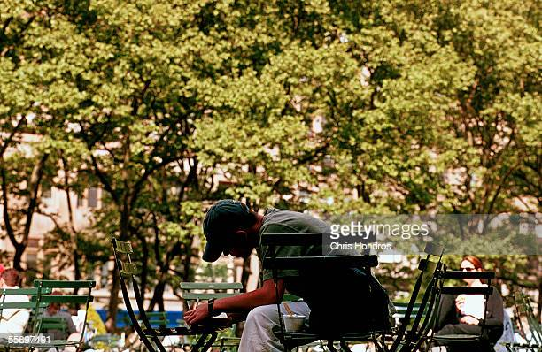 A man writes on a chair in the shadow of the foliage May 14 2001 New York Citys Bryant Park Pollen counts are particularly high in New York this year