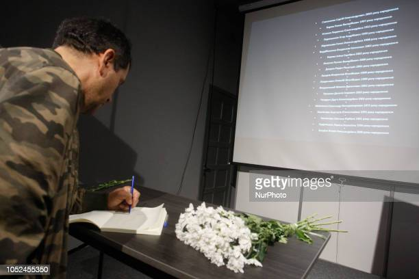 A man writes on a remembrance book in tribute of the victims of a college attack in the Crimean port city of Kerch in the Crimean House in Kiev...