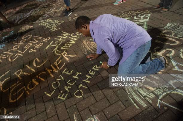 Man writes on the sidewalk in Charlotte, North Carolina, on September 23, 2016 where Justin Carr was shot on September 21 during a demonstration...