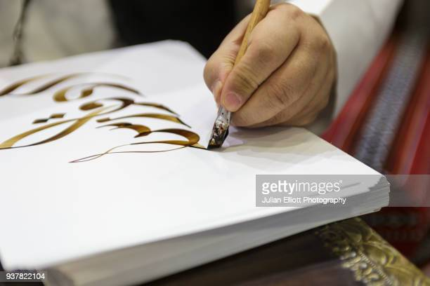 a man writes out traditional arabic script. - arabic script stock pictures, royalty-free photos & images