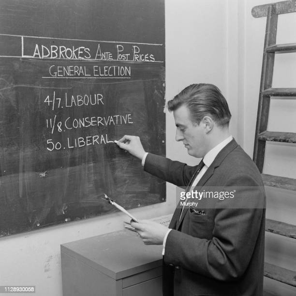 Man writes the general election forecasts on a blackboard at betting company Ladbrokes, UK, 18th October 1963.