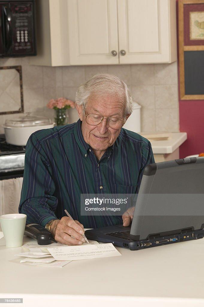 Man writing and using laptop : Stockfoto