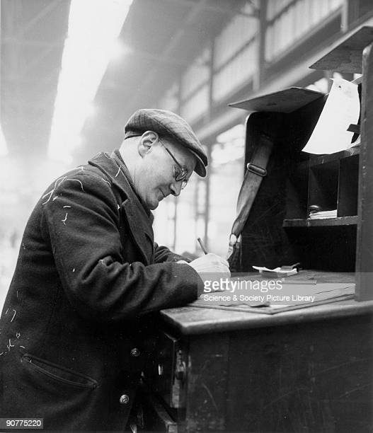 Man writing at a desk in a railway goods depot