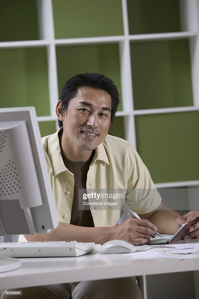 Man writing check by computer : Stockfoto