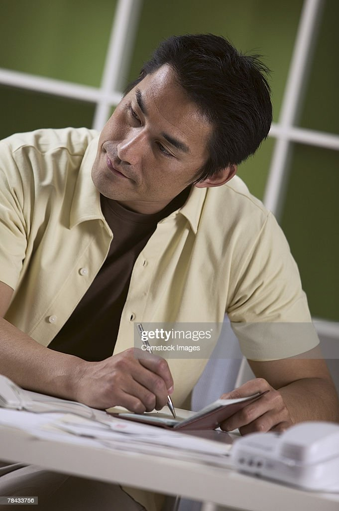 Man writing check : Stockfoto