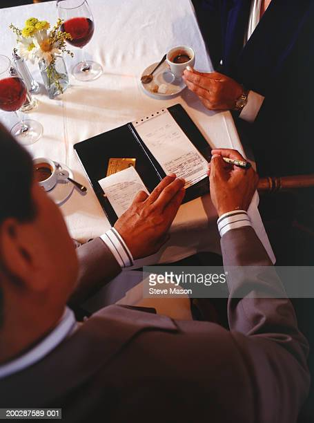 Man writing cheque in restaurant, elevated view