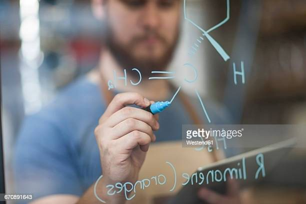 Man writing formula on glass pane