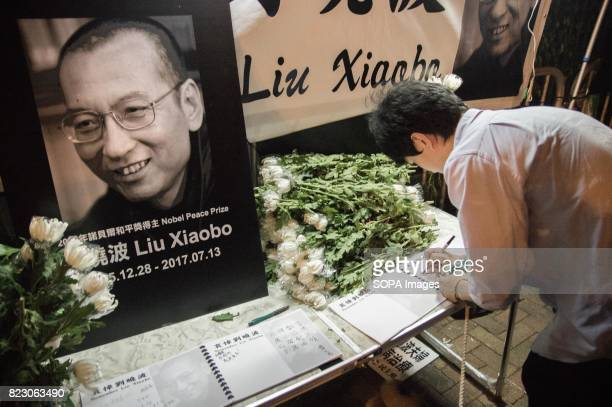 A man writing his message in the memorial book for Liu Xiaobo Residents of Hong Kong hosted a vigil service outside the Chinese Liaison Office of...