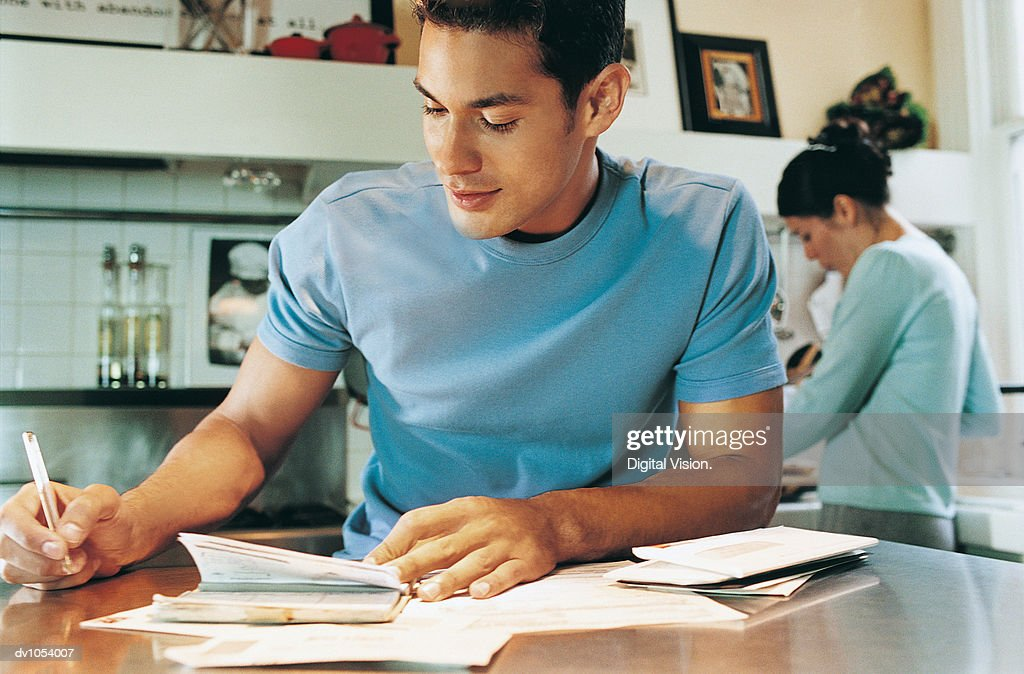 Man Writing in a Diary, Woman in the Background : Stock Photo