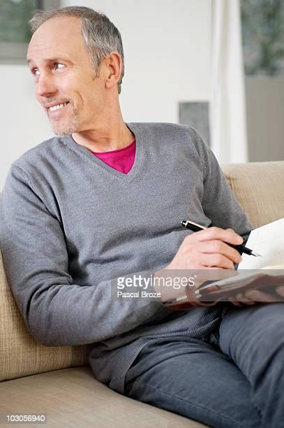 Man writing in a personal organizer