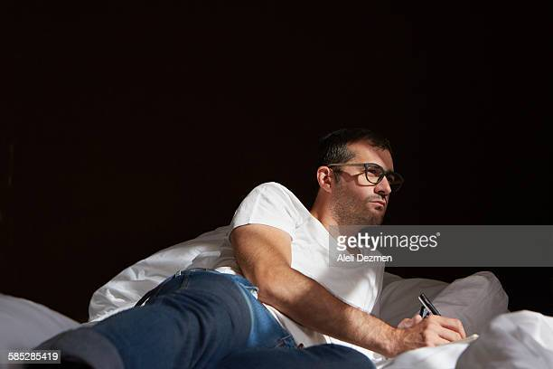 Man writing in bed