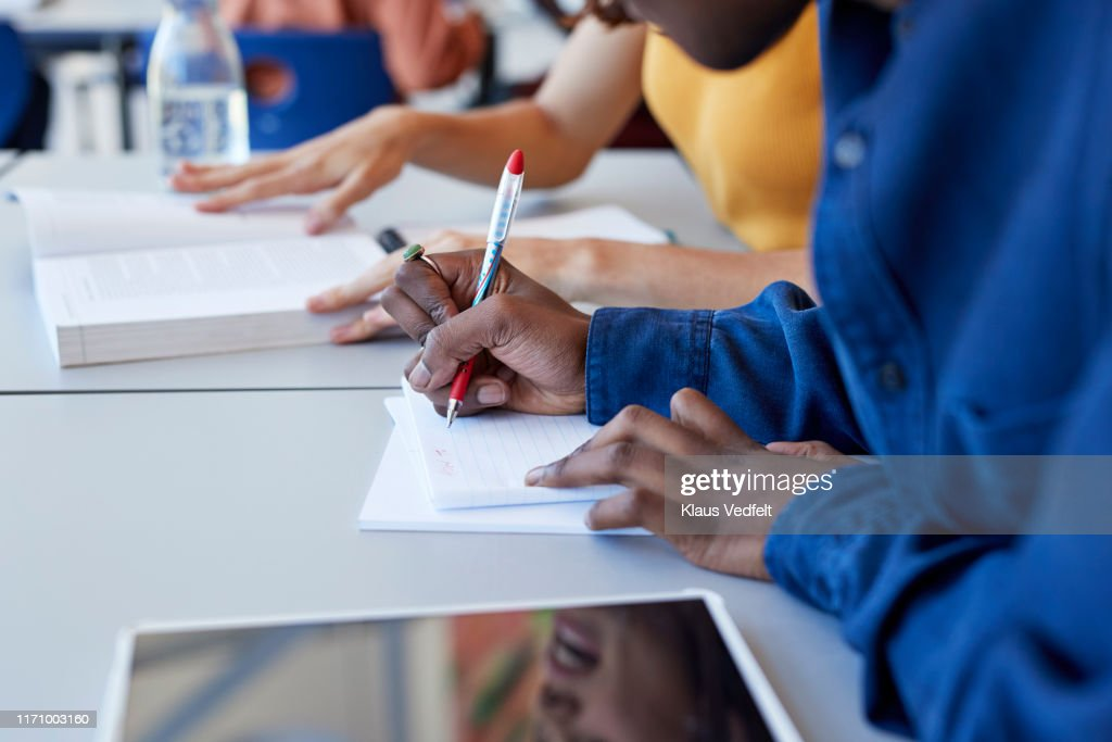 Man writing in book while sitting with friend : Stock Photo