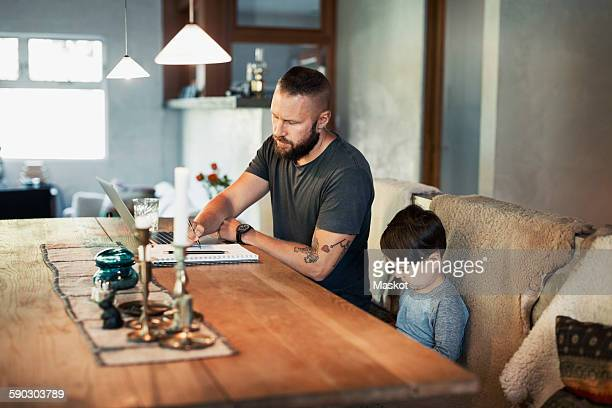 Man writing in book while son sitting at dining table