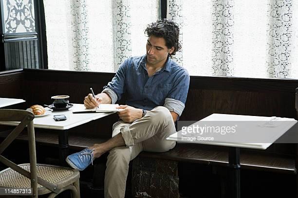 Man writing in coffee shop