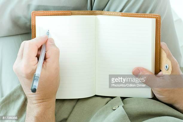 man writing in diary, cropped view of hands - linkshandig stockfoto's en -beelden