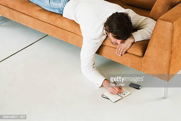 man writing in diary, lying on sofa - human body part stock pictures, royalty-free photos & images
