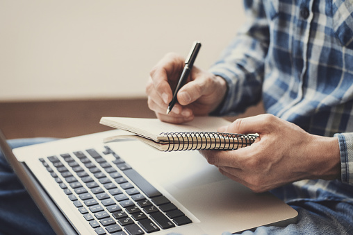 Man writing in notebook 840602536