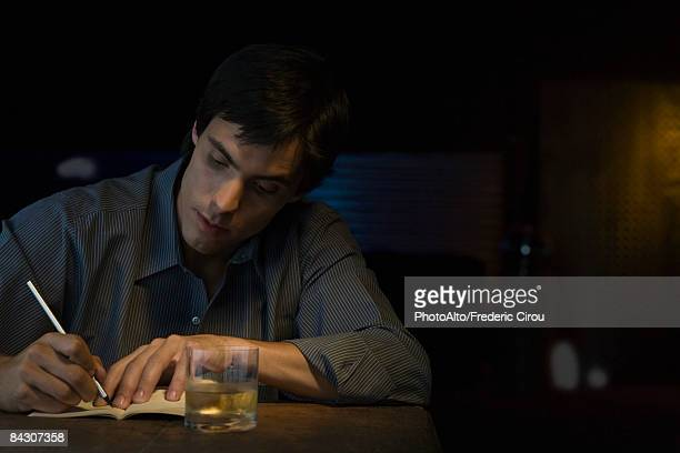 man writing in notebook, sitting in bar - authors foto e immagini stock