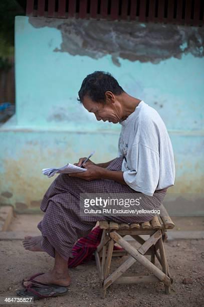 Man writing in notepad, Bagan, Myanmar